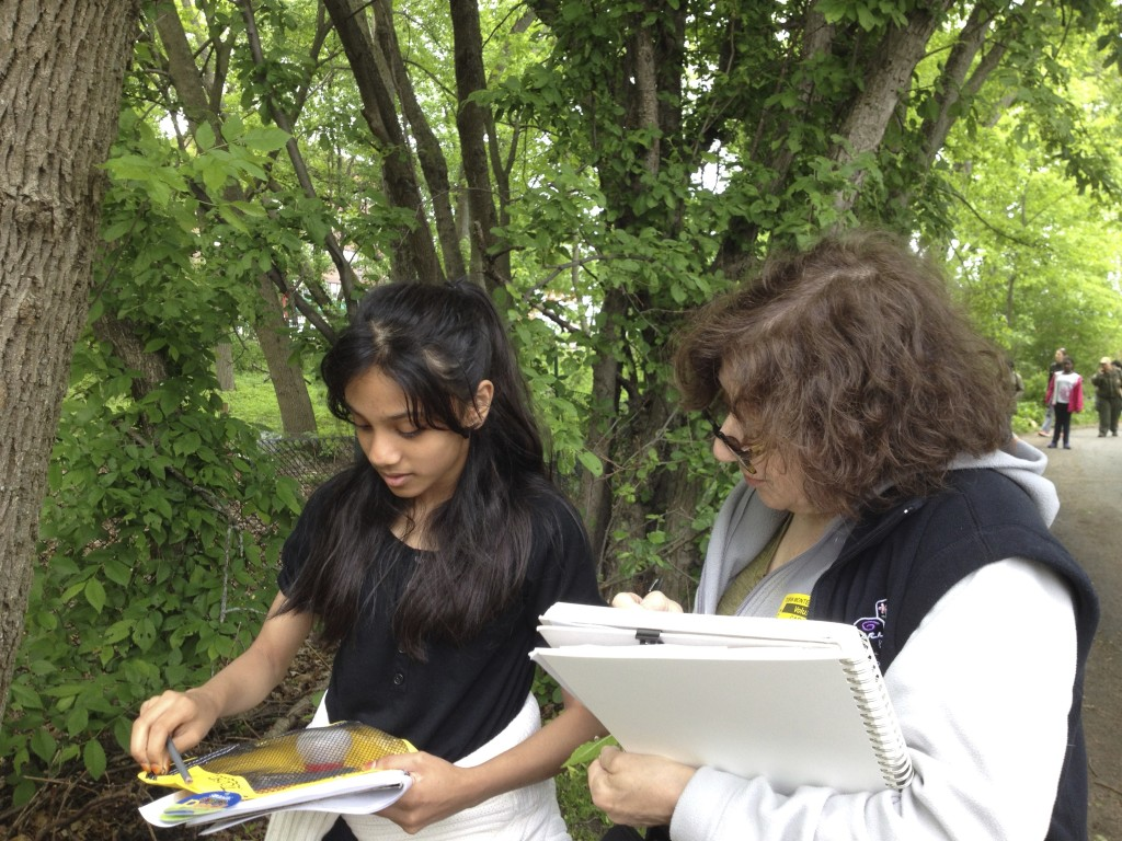 female mentor looking at a students sketchbook outdoors