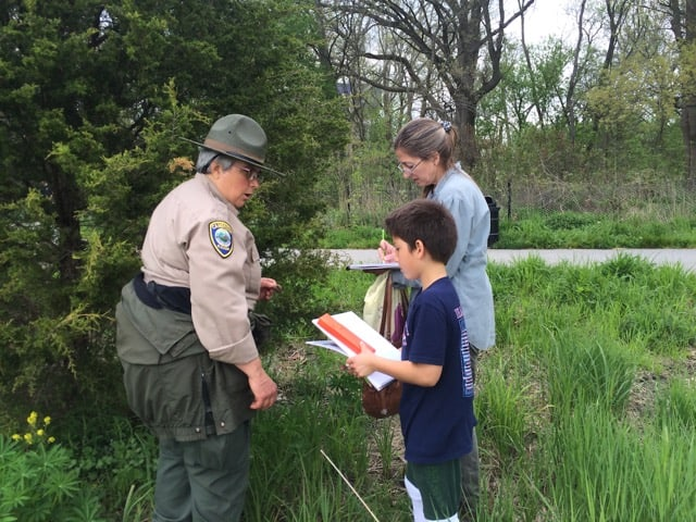 A female ranger in a green hat and uniform talking to an adult and s child who both hold notebooks, outdoors.