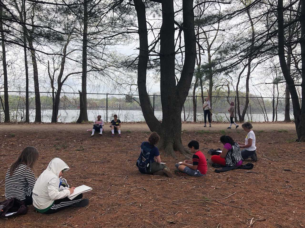 five pairs of adults and children are spread out in a pine grove with water in the backround