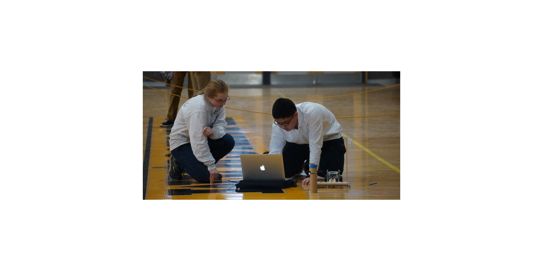two high school students preparing a contraption for science olympiad