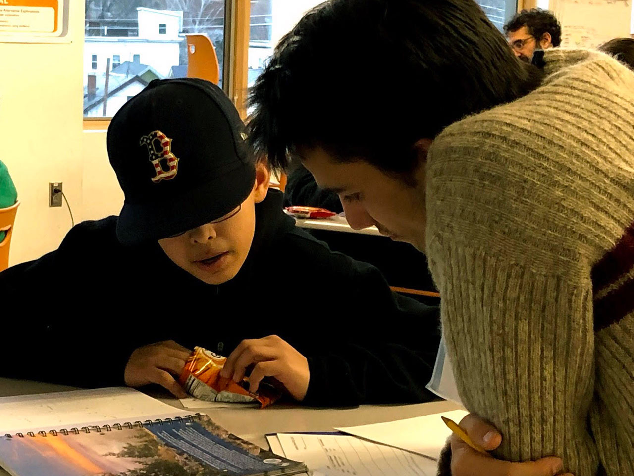 male tutor and male student pore over an assignment at a Learning Center